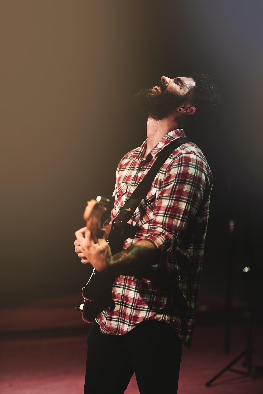 man in plaid sport shirt playing guitar