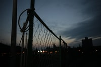 chain link fence under nimbus clouds