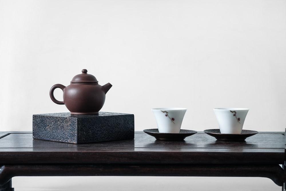 brown teapot on black surface