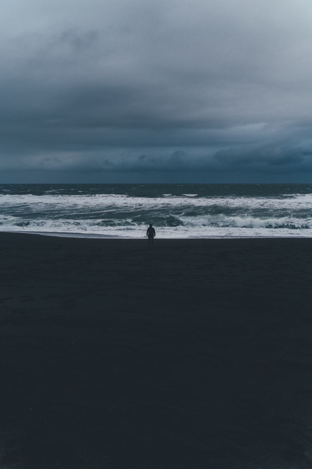 person standing on shore under cloudy sky