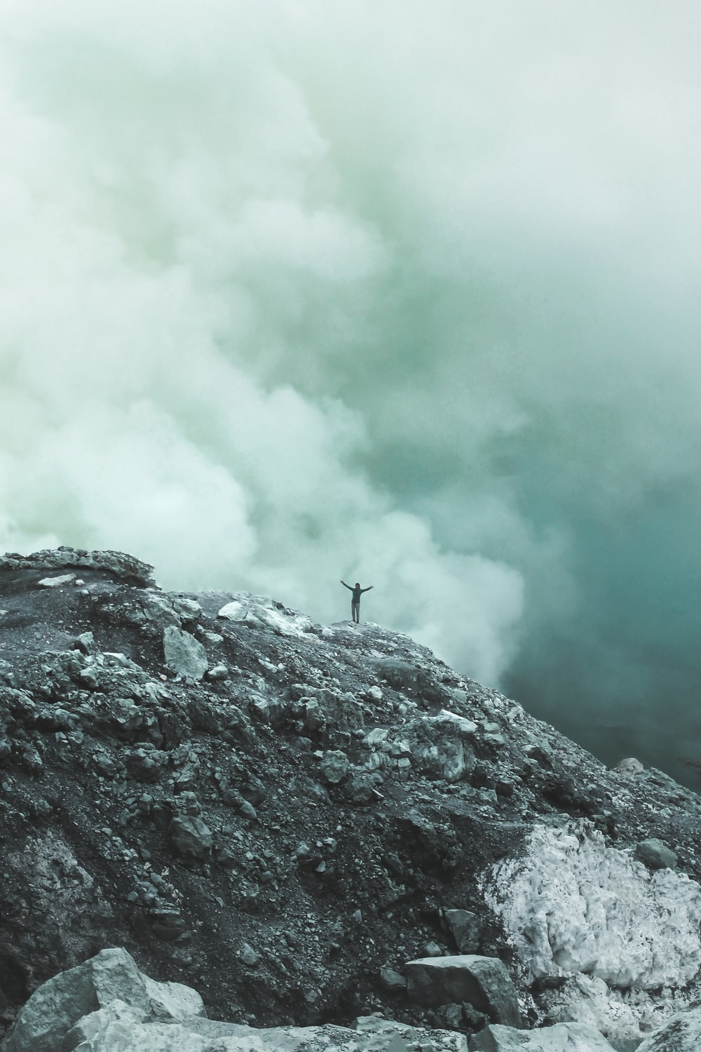 person standing on cliff with clouds background