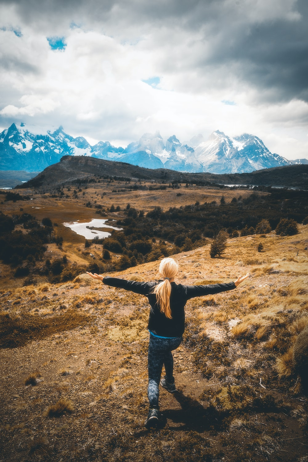 woman standing at middle of mountain