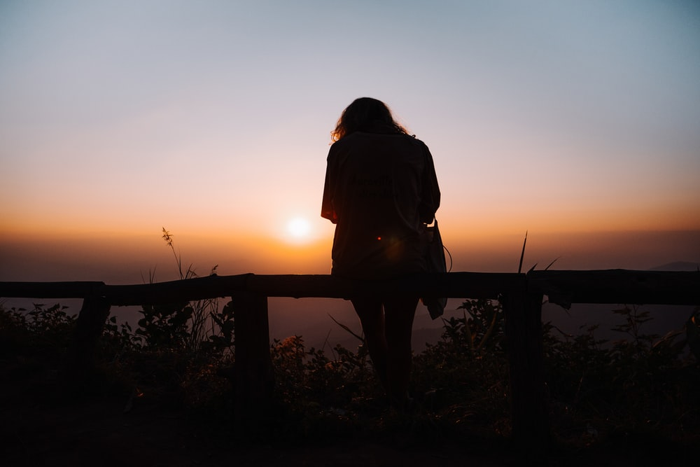 silhouette of woman sitting on brown wooden railling