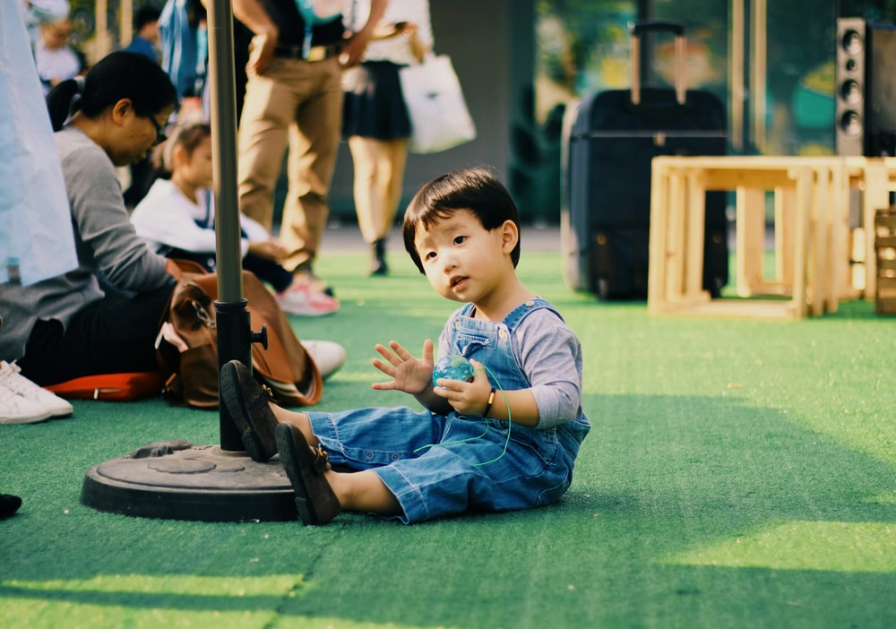 boy in blue overalls sitting on green surface