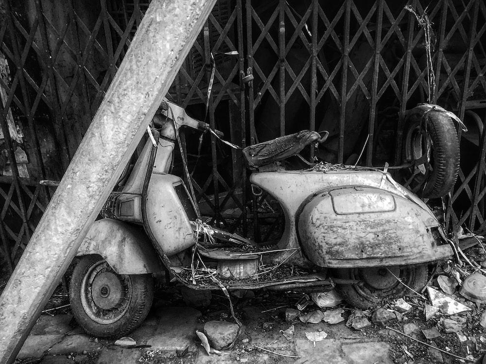 motor scooter beside grey metal gate during daytime