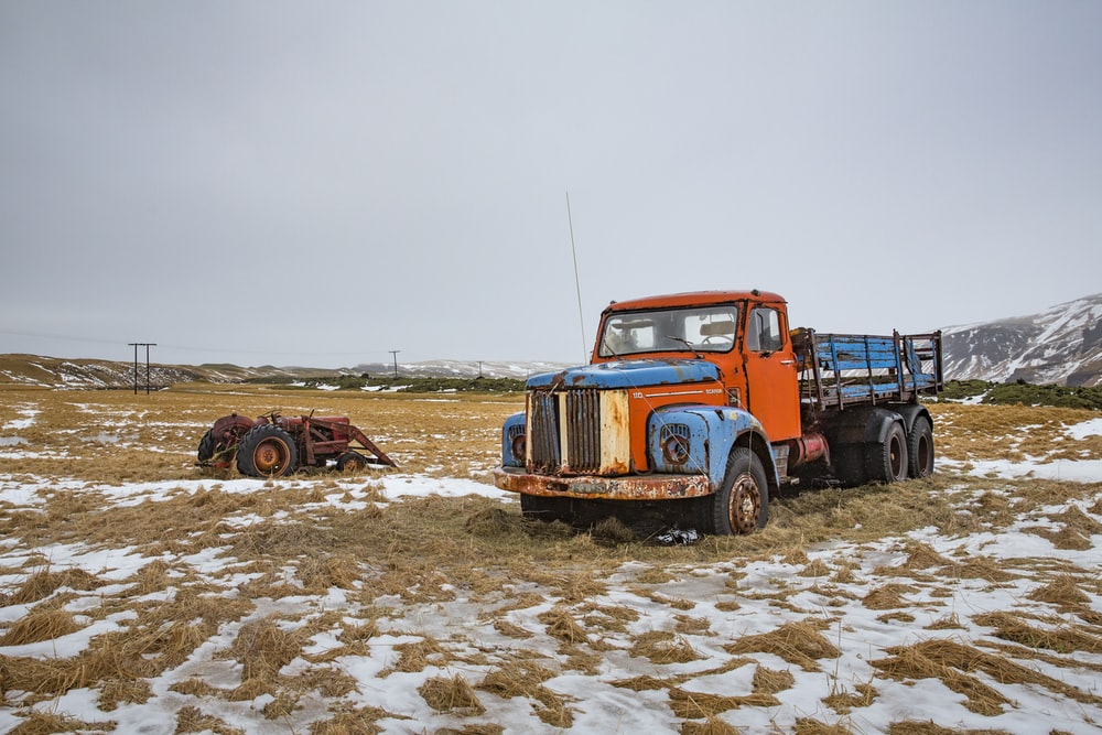 blue and orange stake truck on field near brown farm tractor