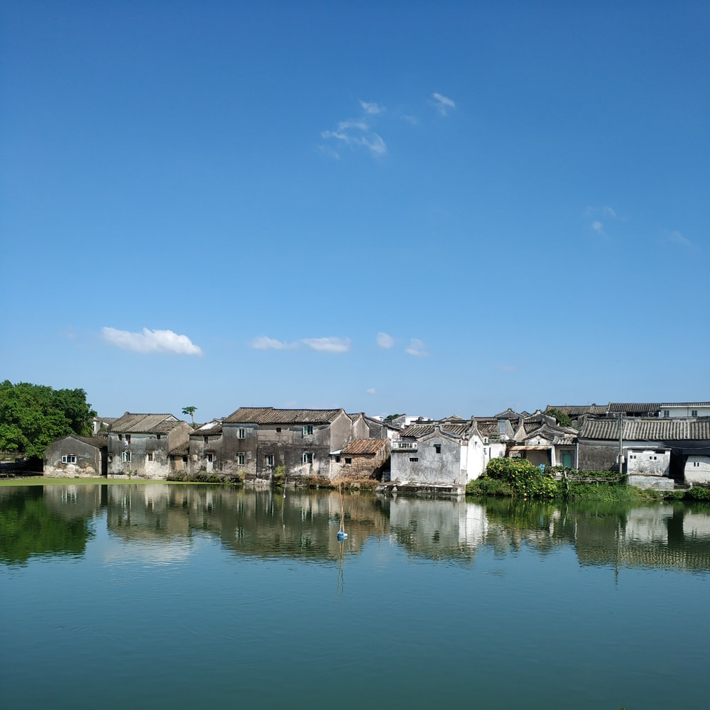 reflective photography of village near body of water