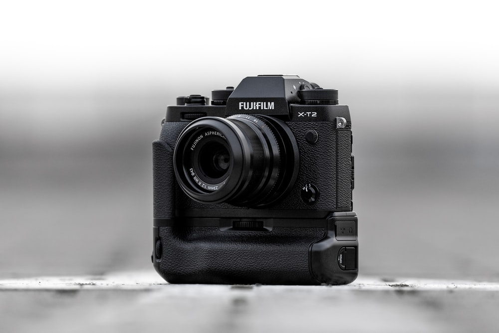 black Fujifilm camera in grayscale photo