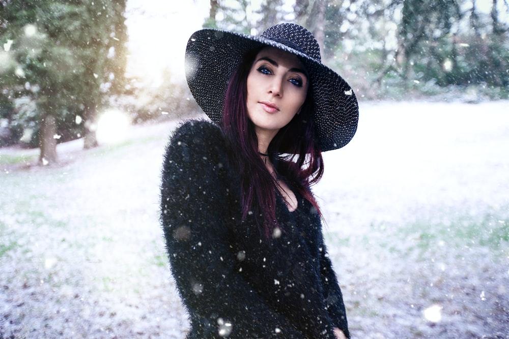 woman wearing black sun hat standing near trees during daytime
