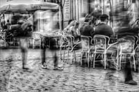 grayscale photography of people sitting on bistro chairs