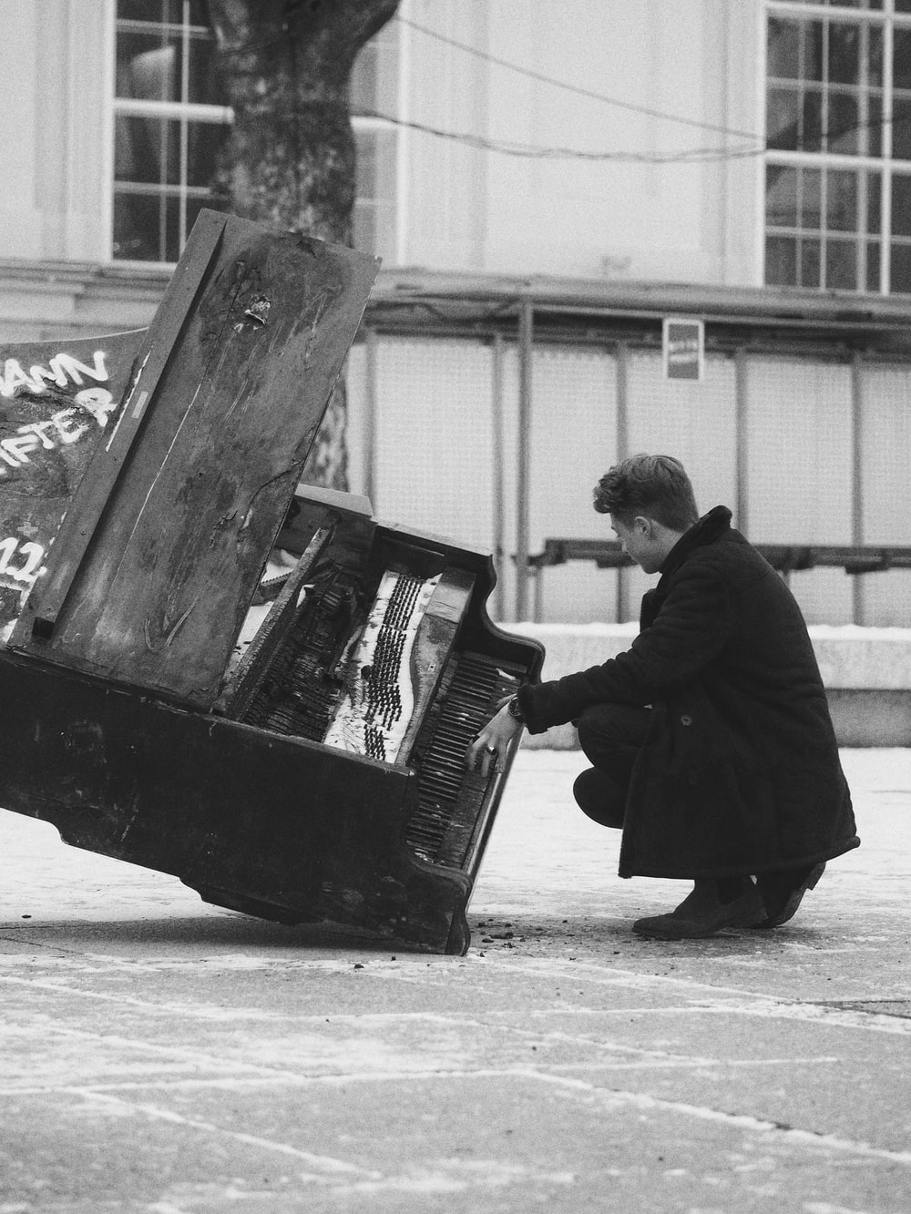 grayscale photography of man crouching in front of damaged piano
