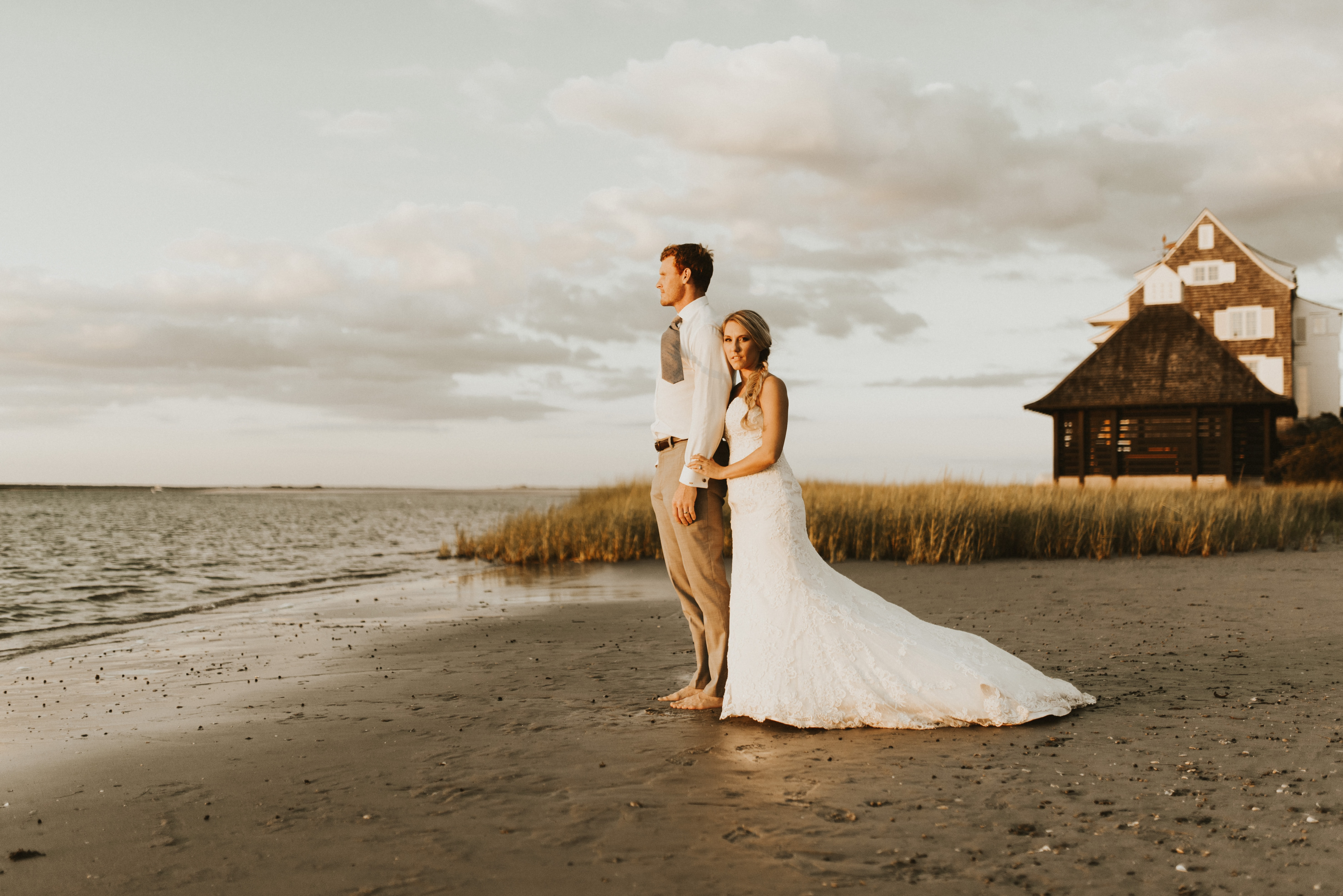couple standing beside beach during daytime