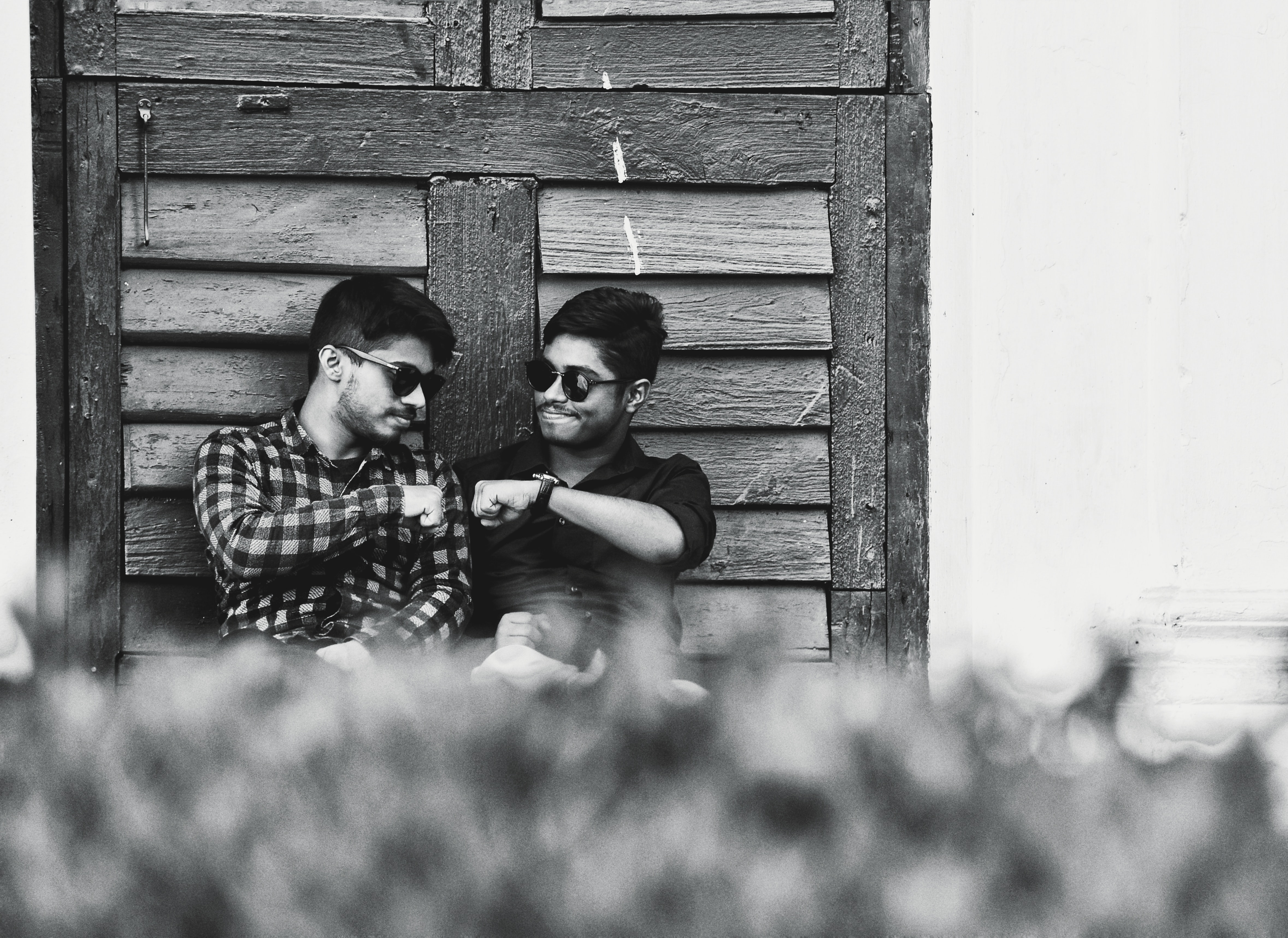 two men sitting while doing fist bomb grayscale photo