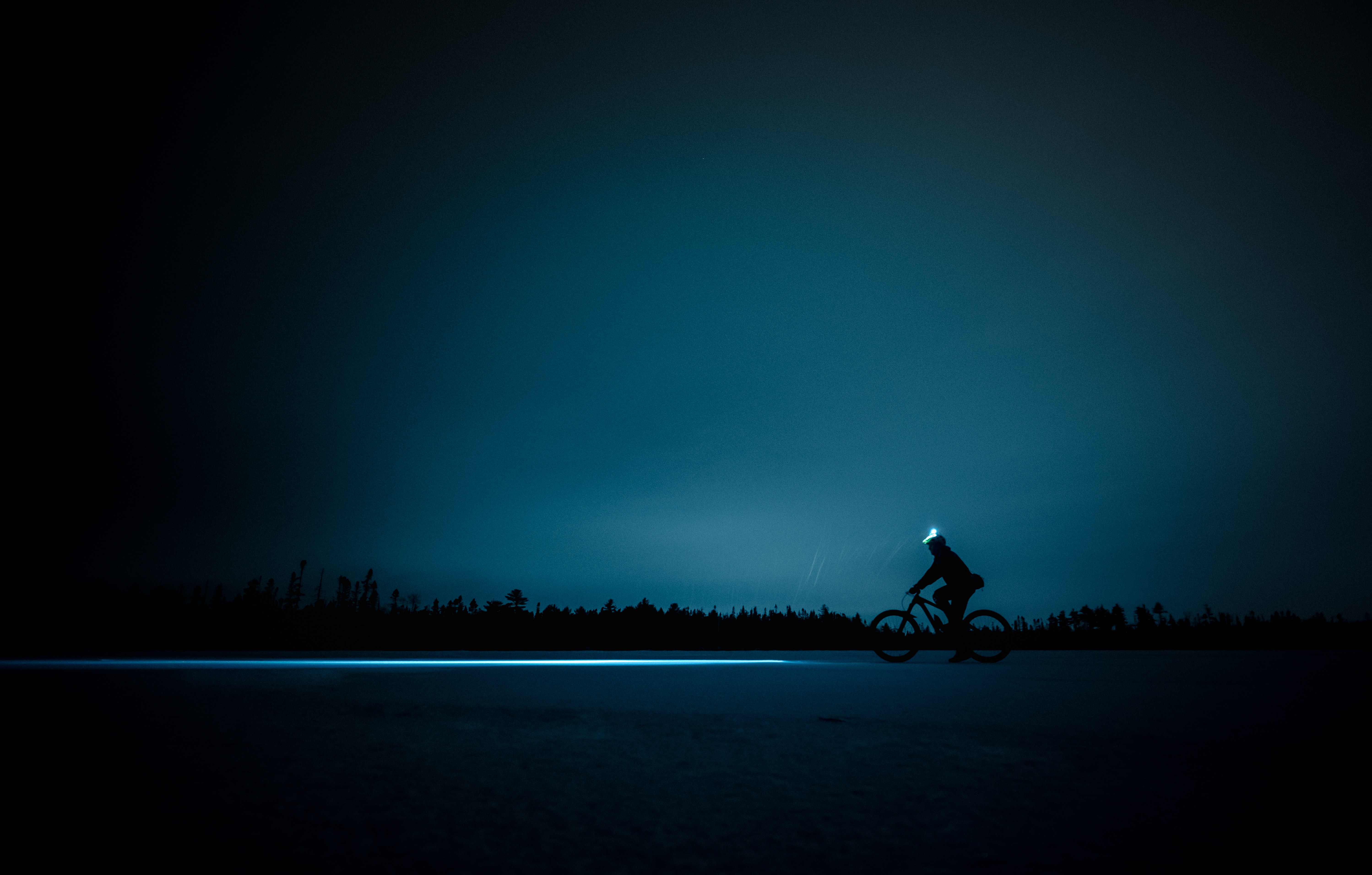 silhouette of person cycling during night