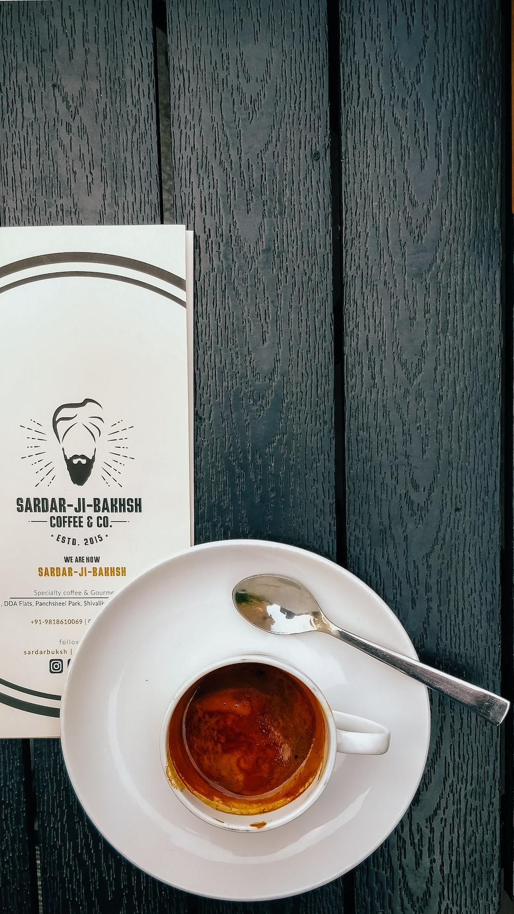 coffee in white ceramic mug near teaspoon