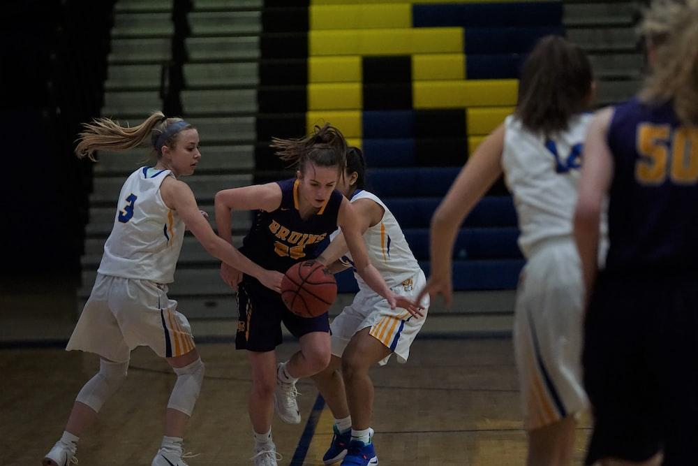women playing basketball on court