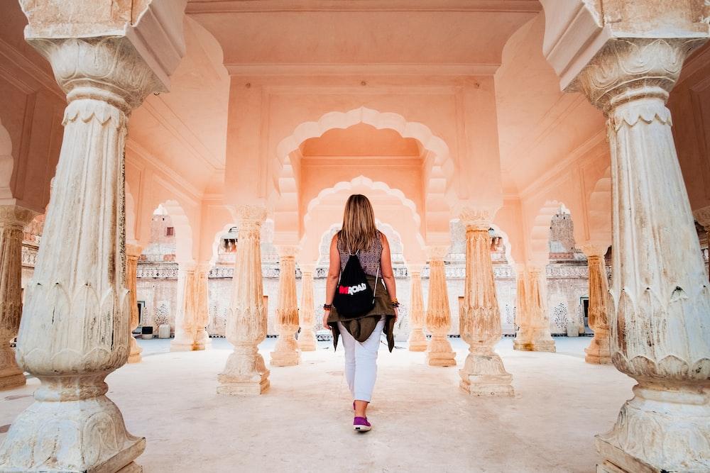 woman walking under pink building
