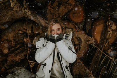 woman leaning on woods covering her face