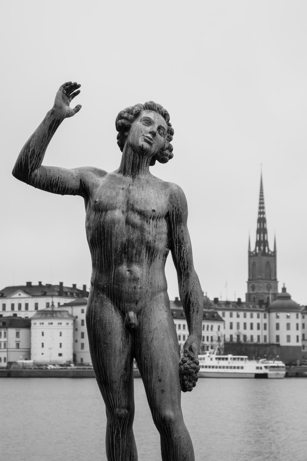 grayscale photography of topless man statue