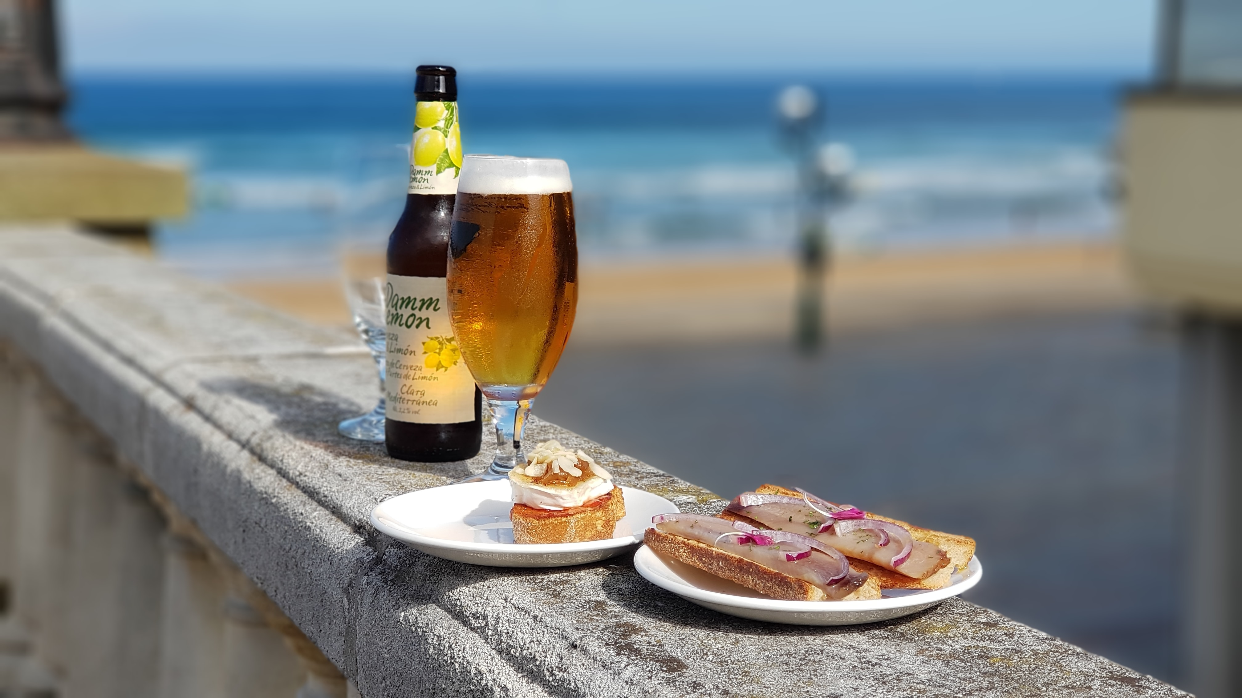 bread on plate beside glass of beer at daytime