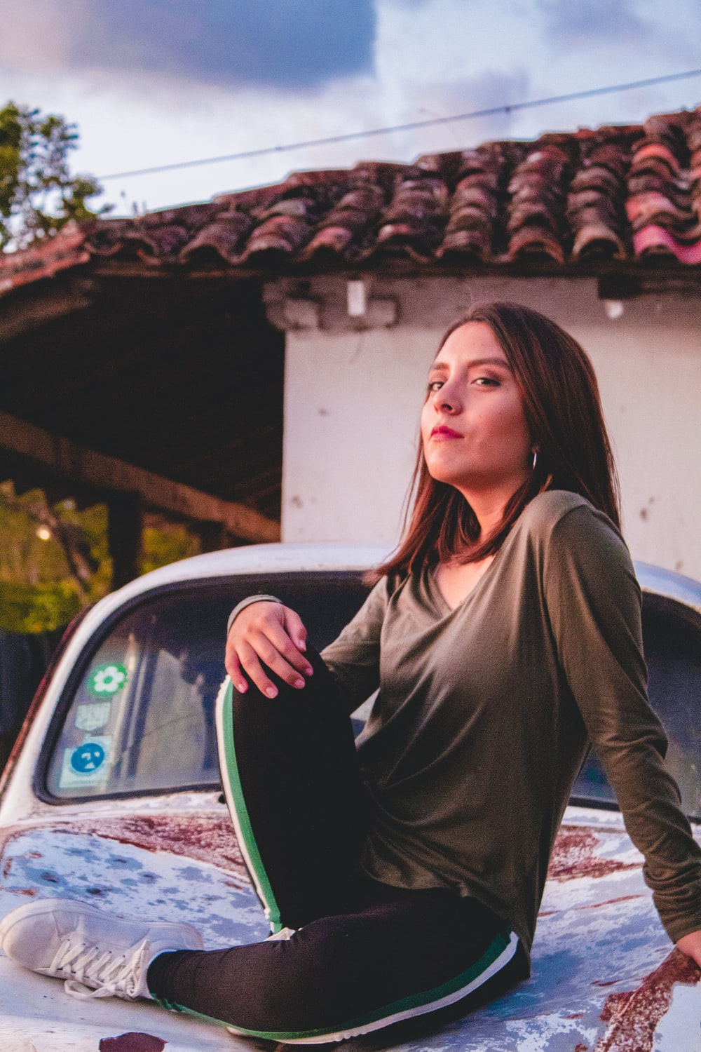 woman sitting on vehicle near house during daytime
