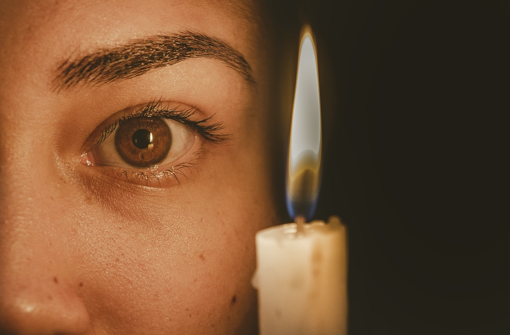 lighted candle beside human eye in close-up photography