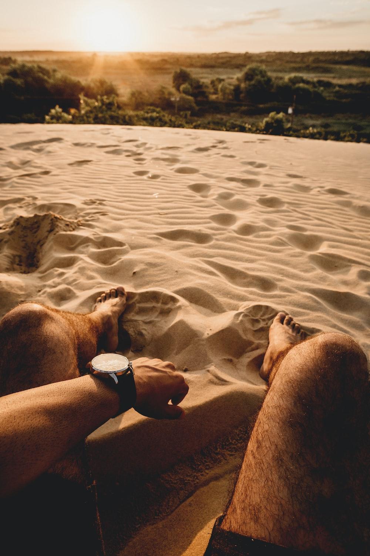 man sitting on sand during daytime