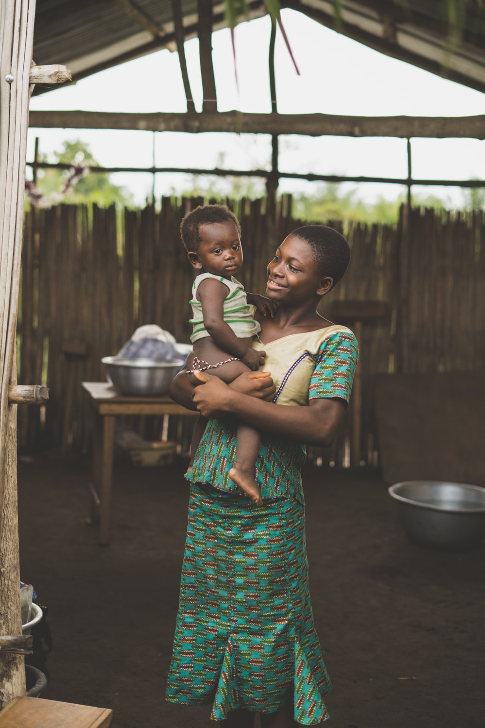 smiling woman standing while holding baby