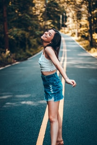 shallow focus photo of woman standing on the center of the road during daytime