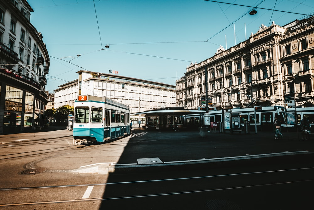 train at middle of street surrounded by buildings