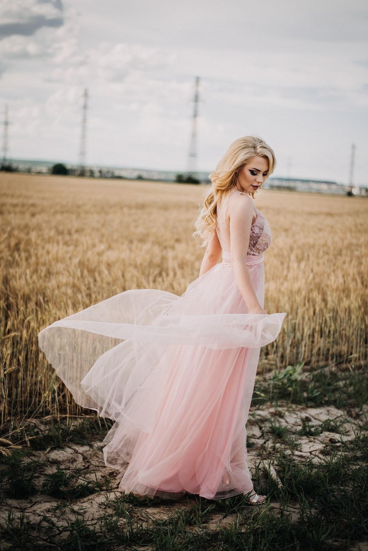 woman wearing pink empire-waist dress standing beside wheat field