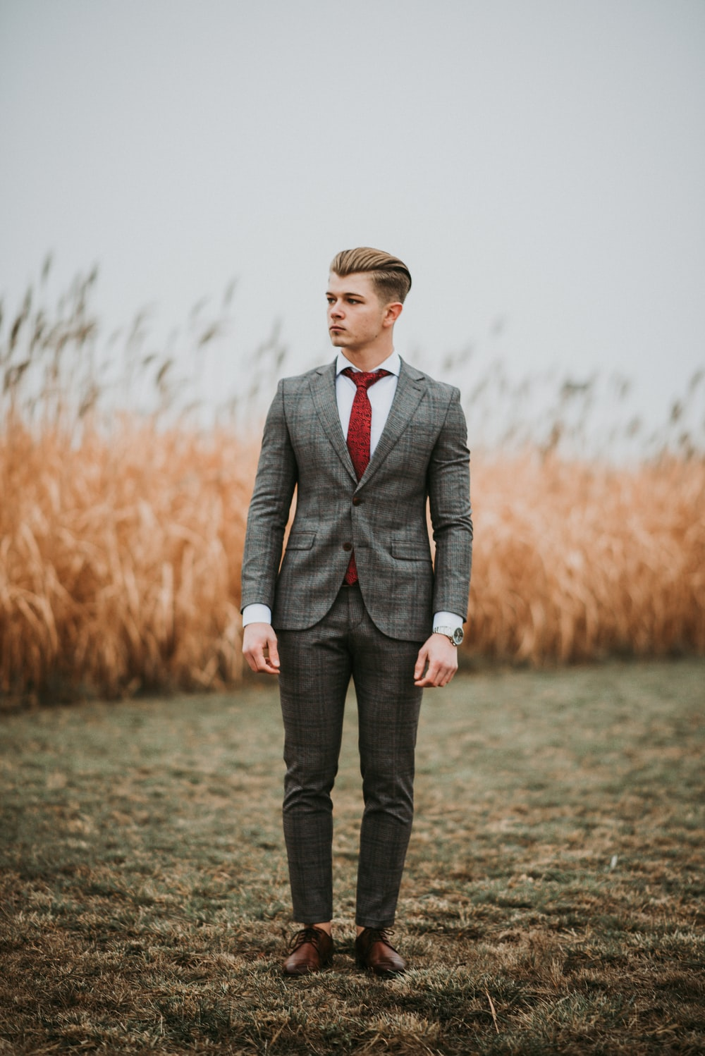 man standing near brown grass field on selective focus photography