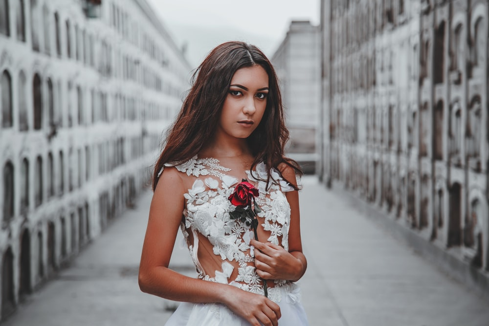 woman standing in between buildings while holding red flower