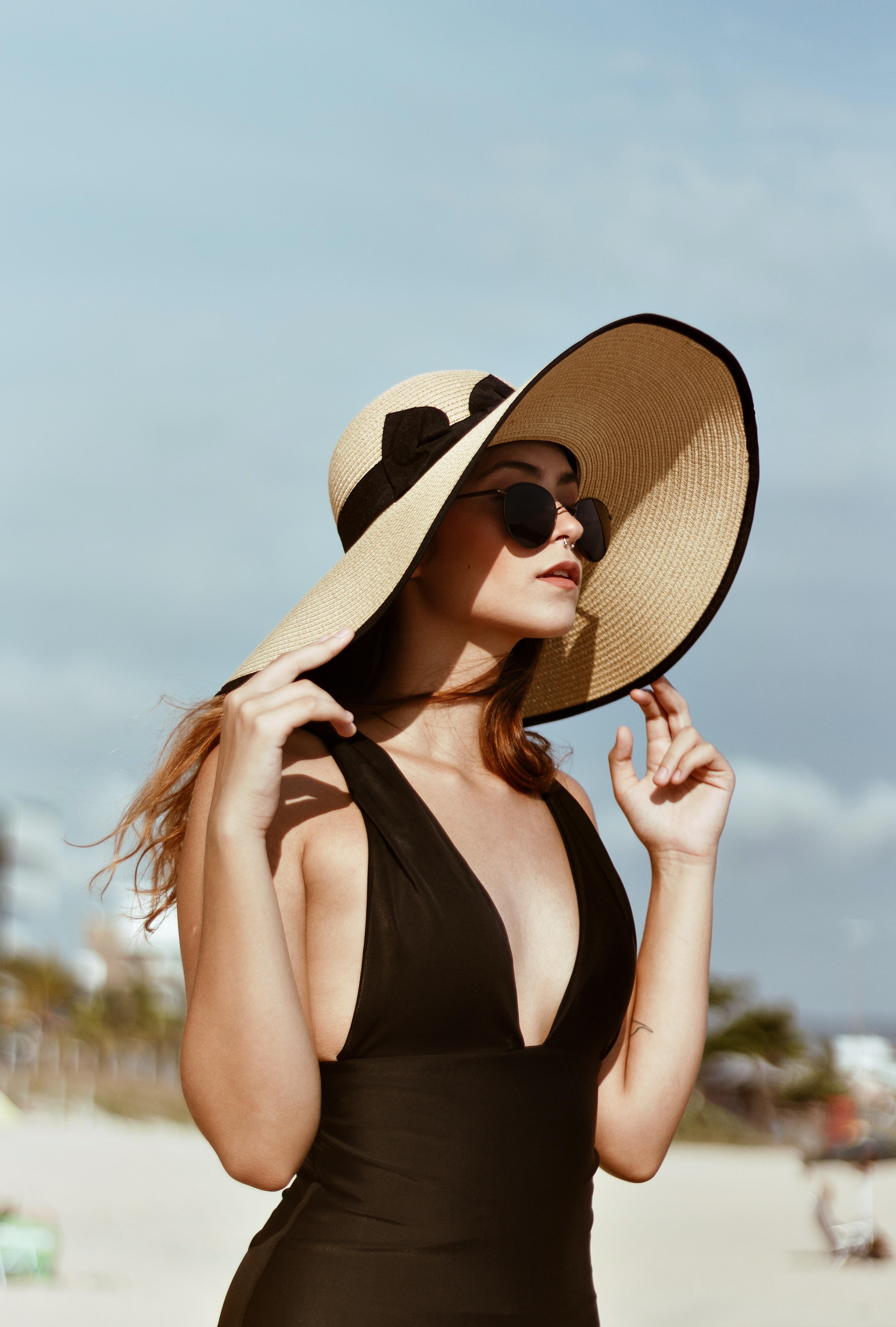 woman wearing beach hat under white sky