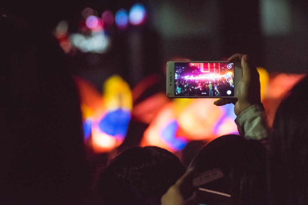 person taking photo of pink light