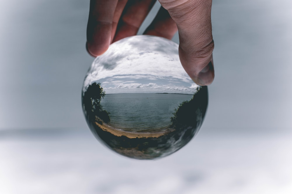 person holding orb with image of sea