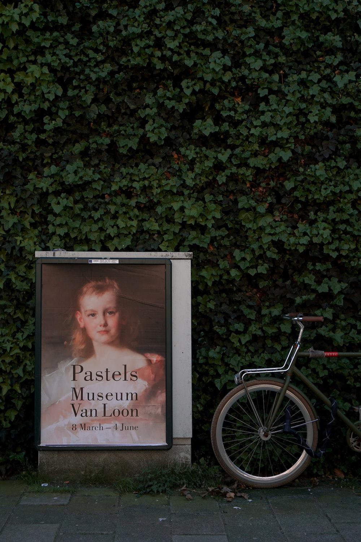 Pastels Museum Van Loon poster beside bike parked on green-leafed wall