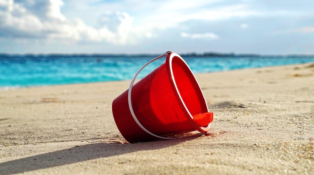 red plastic bucket on seashore