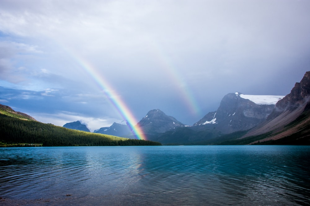 blue lake and rainbow under nimbus clouds