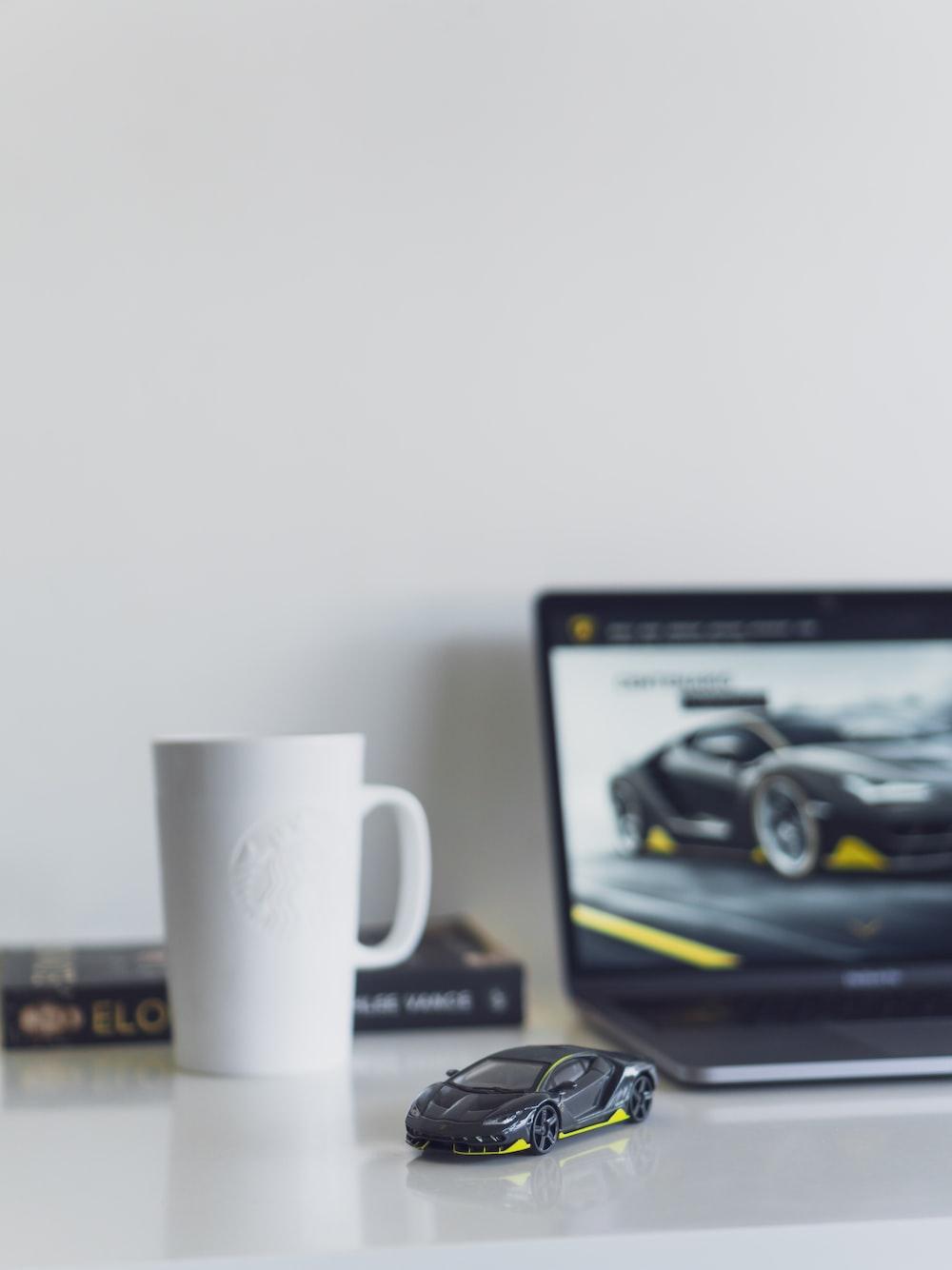 black sports car miniature beside white mug