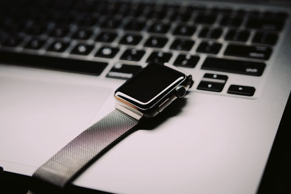 space gray Apple watch with silver mesh band