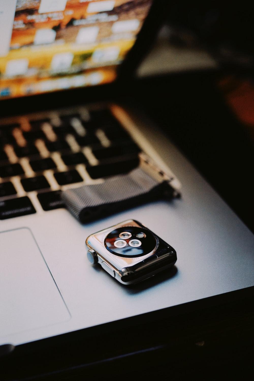 silver Apple watch on MacBook Pro