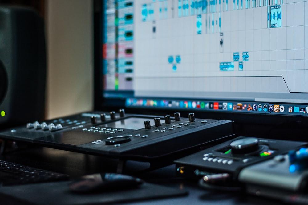 black audio mixer beside turned-on flat screen monitor