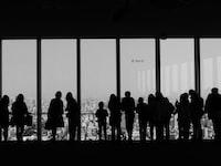 people overlooking buildings inside room