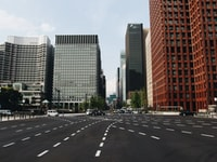 vehicles travelling on road near high-rise buildings during daytime