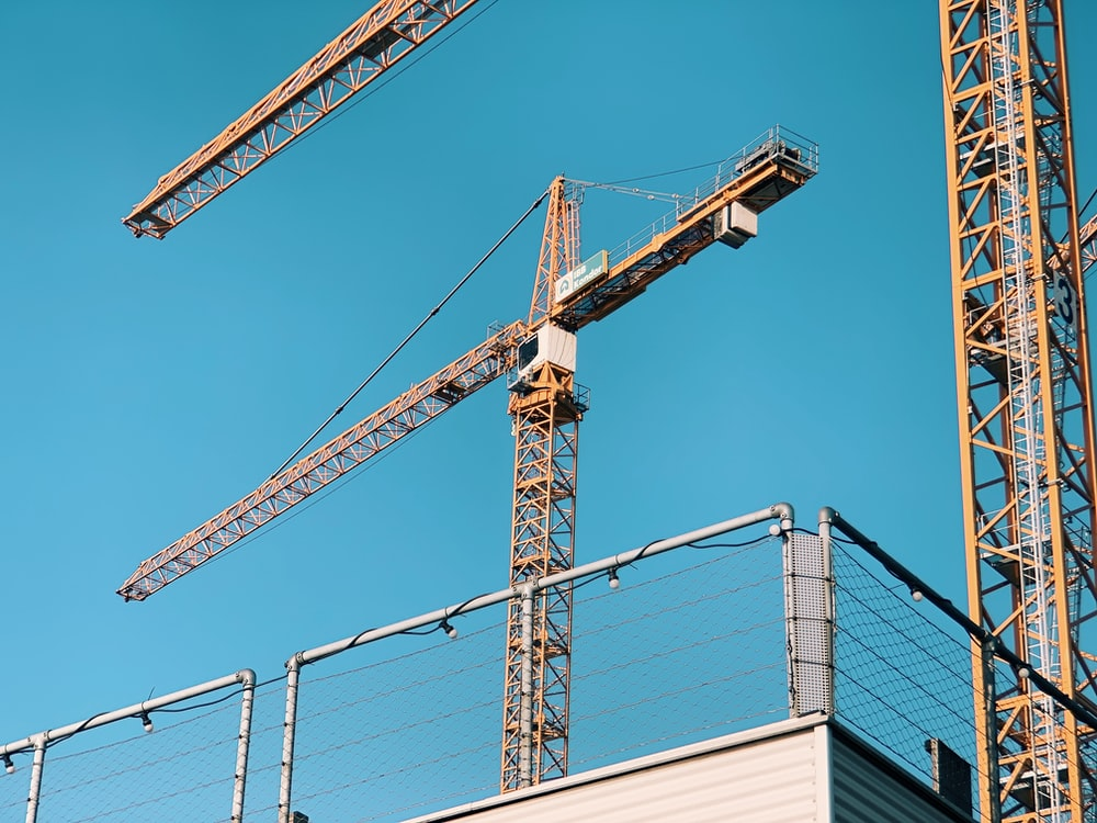 two yellow t-cranes under blue sky