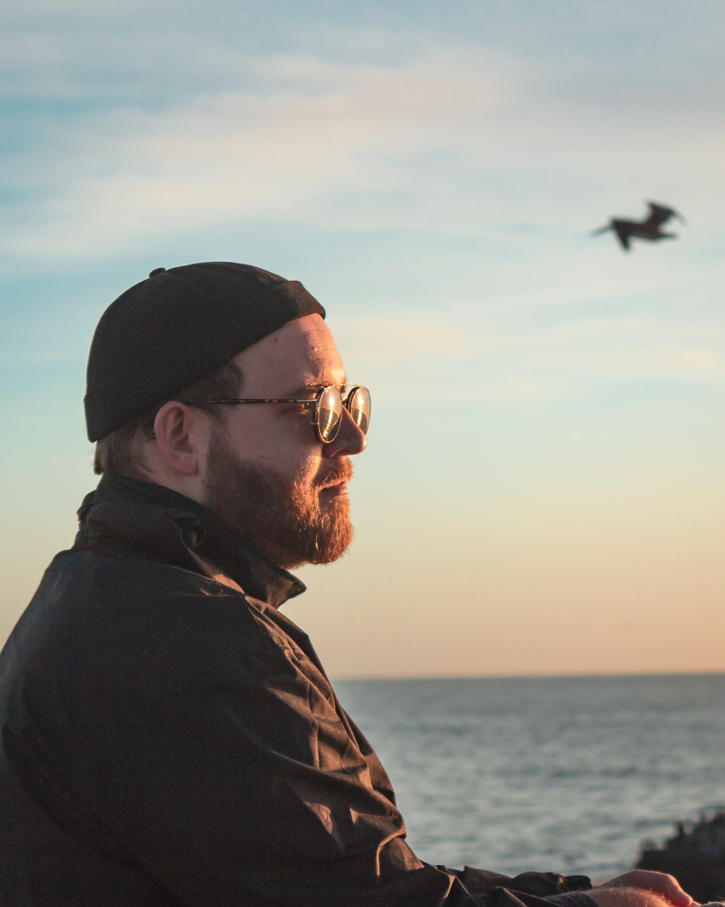 man wearing black knit cap overlooking on sea