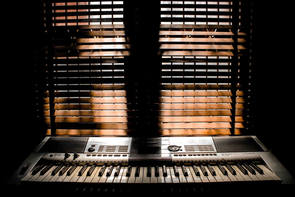 gray electronic keyboard placed in front of window blinds