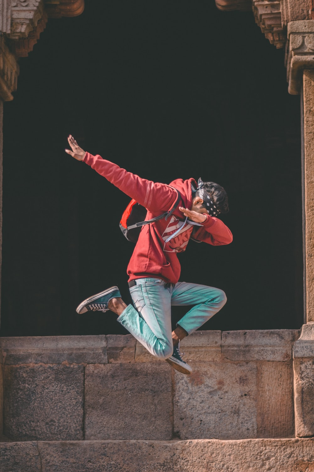 man jumping while raising hands in slant position