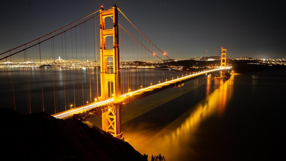 suspension bridge beside body of water